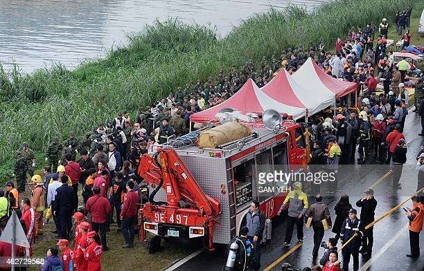 Rescue personnel military and members of the media line up along the shore as rescue operations continue to free passengers from a TransAsia ATR...