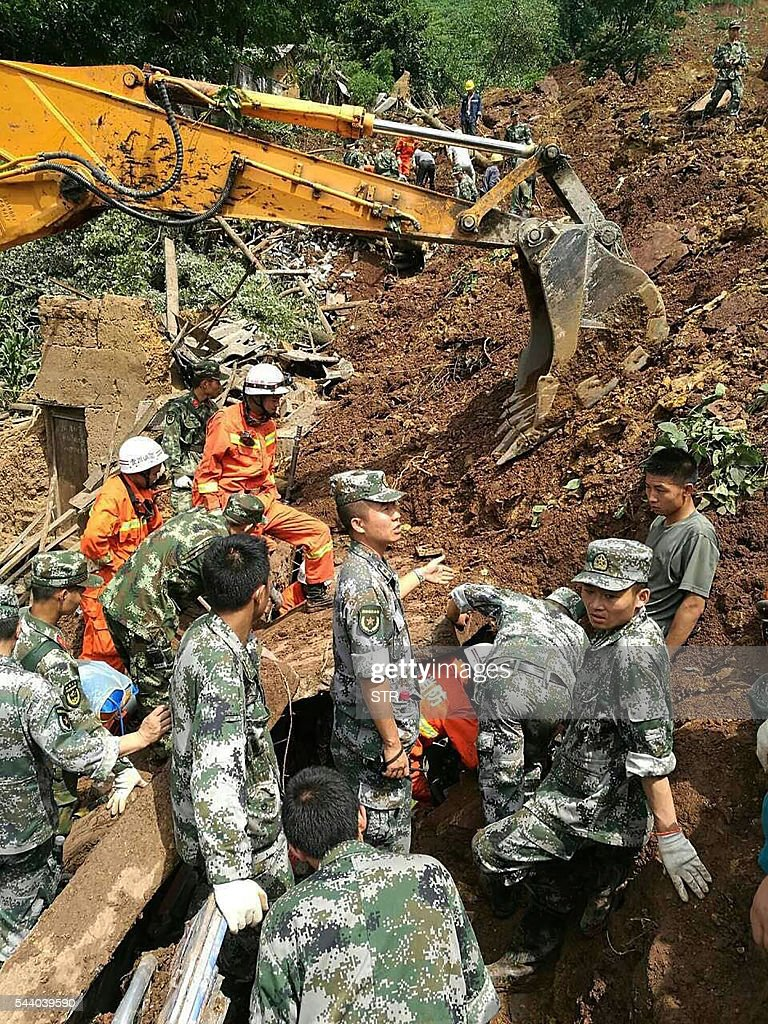 Rescue personnel search for survivors of a landslide at Pianpo village in China's southwest Guizhou province on July 1, 2016. Heavy rain caused a landslide in southwestern China on July 1 that killed at least six and left 17 others missing, local officials said. / AFP / STR / China OUT