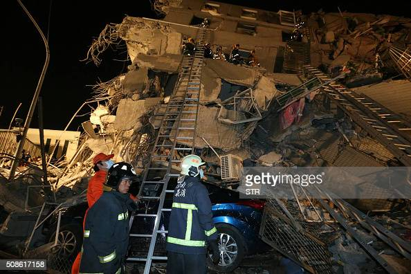 Rescue personnel search through debris at the site of a collapsed building in the southern Taiwanese city of Tainan following a strong 64magnitude...