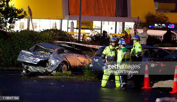 Rescue personnel stand next to destroyed cars outside the Albany Shopping Centre in the North Shore of Auckland on May 3 2011 after a freak tornado...