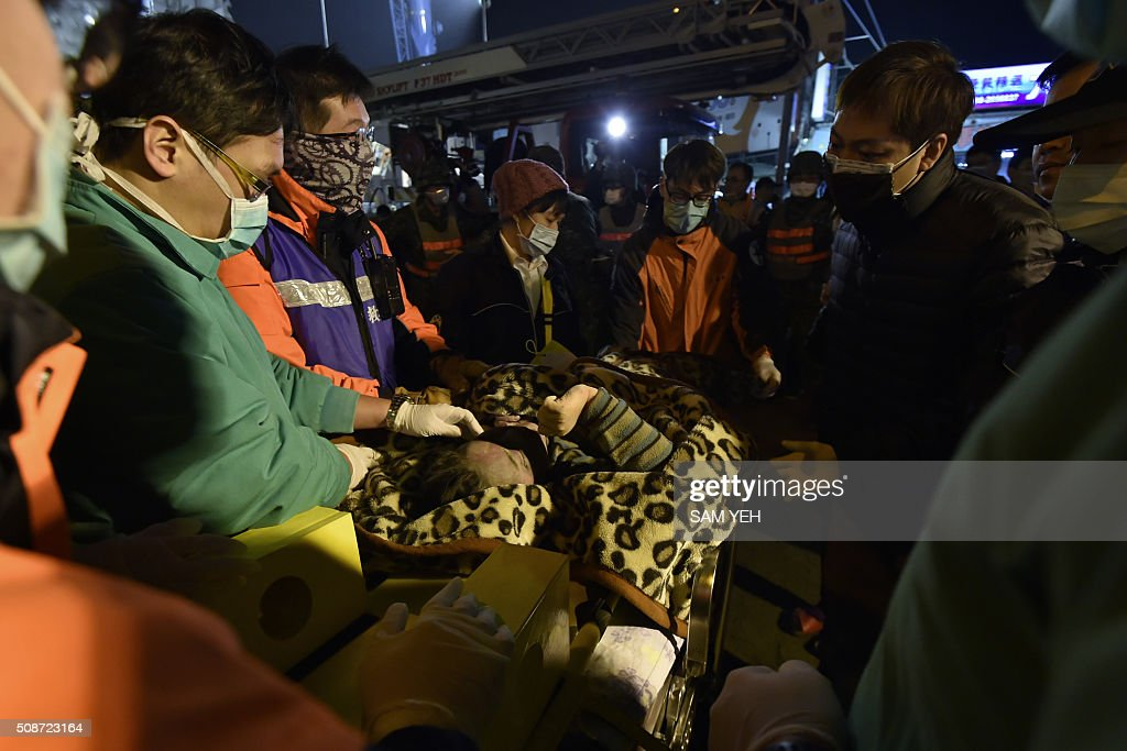 Rescue personnel tend to a survivor pulled from the site of a collapsed building in the southern Taiwanese city of Tainan on February 6, 2016 following a strong 6.4-magnitude earthquake. A powerful earthquake in Taiwan felled a 16-storey apartment complex full of families who had gathered for Lunar New Year celebrations in the early hours of February 6, with at least seven dead and more than 30 feared trapped. AFP PHOTO / Sam Yeh / AFP / SAM YEH