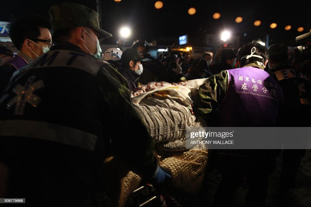 Rescue personnel use a stretcher to take a victim to an ambulance at the site of a collapsed building in the southern Taiwanese city of Tainan on February 6, 2016 following a strong 6.4-magnitude earthquake. More than 250 people have been rescued from the Wei-kuan apartment complex in the southern city of Tainan since the quake hit at 4:00 am Saturday, killing 14 people and toppling four blocks of around 100 homes in total. WALLACE