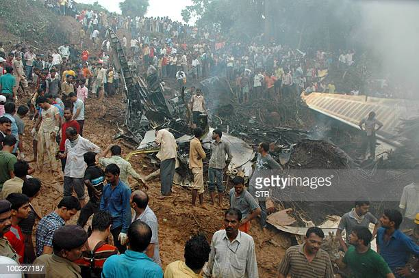 Rescue personnel volunteers and onlookers are seen near the smouldering wreckage of an Air India Boeing 737800 aircraft which crashed upon landing in...