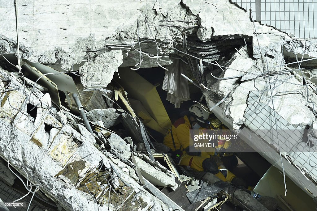Rescue personnel work amid rubble at the site of a collapsed building in the southern Taiwanese city of Tainan on February 6, 2016 following a strong 6.4-magnitude earthquake. A powerful earthquake in Taiwan felled a 16-storey apartment complex full of families who had gathered for Lunar New Year celebrations in the early hours of February 6, with at least seven dead and more than 30 feared trapped. AFP PHOTO / Sam Yeh / AFP / SAM YEH