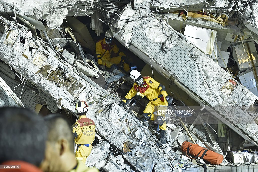 Rescue personnel work at the site of a collapsed building in the southern Taiwanese city of Tainan on February 6, 2016 following a strong 6.4-magnitude earthquake. A powerful earthquake in Taiwan felled a 16-storey apartment complex full of families who had gathered for Lunar New Year celebrations in the early hours of February 6, with at least seven dead and more than 30 feared trapped. AFP PHOTO / Sam Yeh / AFP / SAM YEH
