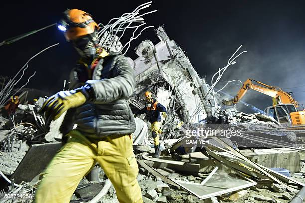 Rescue personnel work at the site of a collapsed building in the southern Taiwanese city of Tainan on February 6 2016 following a strong 64magnitude...