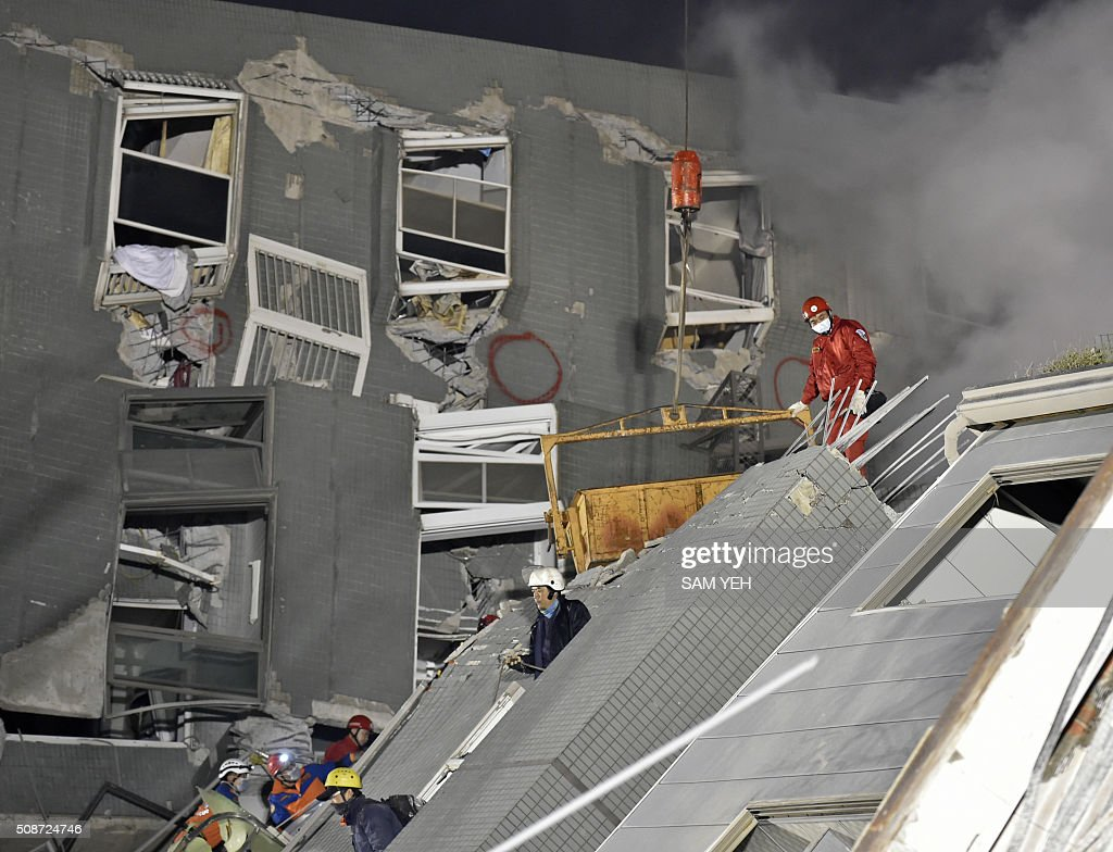 Rescue personnel work at the site of a collapsed building in the southern Taiwanese city of Tainan on February 6, 2016 following a strong 6.4-magnitude earthquake. A powerful earthquake in Taiwan felled a 16-storey apartment complex full of families who had gathered for Lunar New Year celebrations on February 6, with at least eleven dead and more than 30 feared trapped. AFP PHOTO / Sam Yeh / AFP / SAM YEH