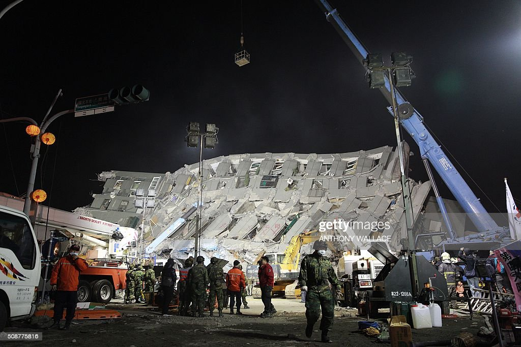 Rescue personnel work at the site of a collapsed building in the southern Taiwanese city of Tainan early on February 7, 2016 following a strong 6.4-magnitude earthquake. More than 250 people have been rescued from the Wei-kuan apartment complex in the southern city of Tainan since the quake hit at 4:00 am Saturday, killing 14 people and toppling four blocks of around 100 homes in total. WALLACE