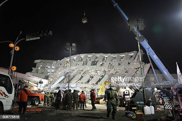 Rescue personnel work at the site of a collapsed building in the southern Taiwanese city of Tainan early on February 7 2016 following a strong...