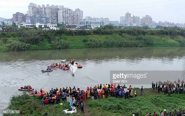Rescue personnel work to free passengers from a TransAsia ATR 72600 turboprop plane that crashlanded into a river outside Taiwan's capital Taipei in...