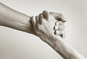 Black and white image of a close up of man's and woman's hand helping.