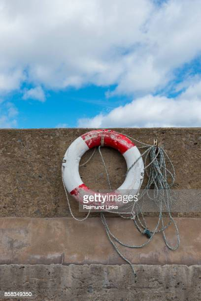 Rescue ring at pier wall in harbor, Seahouses, Northumberland, United Kingdom