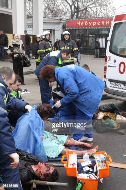 Rescue services and firefighters take care of victims from the Park Kultury metro station on March 29 2010 after an explosion went off in a carriage...