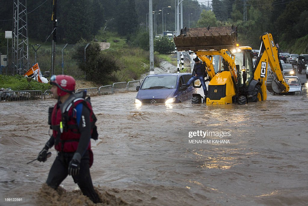 A rescue team evacuates people trapped in their cars in a flooded road near the Israeli-Arab town of Kfar Qara, in central Israel, on January 8, 2013. Stormy weather, including high winds and heavy rainfall, lashed Israel and the Palestinian territories, downing powerlines and trees and blocking roads causing several injuries.