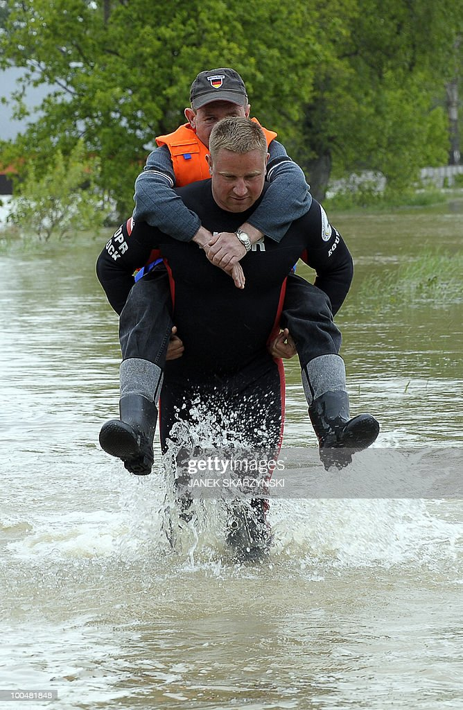 A rescue team member carries a man on his back to help him to escape from a flooded street in Juliszew village in central Poland at Wisla river on May 24, 2010 he death toll from flooding in Poland rose to 15 Monday as torrential rain swelled major rivers to levels unseen in more than a century and rescuers from across Europe battled to prevent further tragedy. Interior Minister Jerzy Miller said flood levels on the Vistula, the country's largest river, were 'worse than expected', raising the risk that flood defences around the capital could burst.