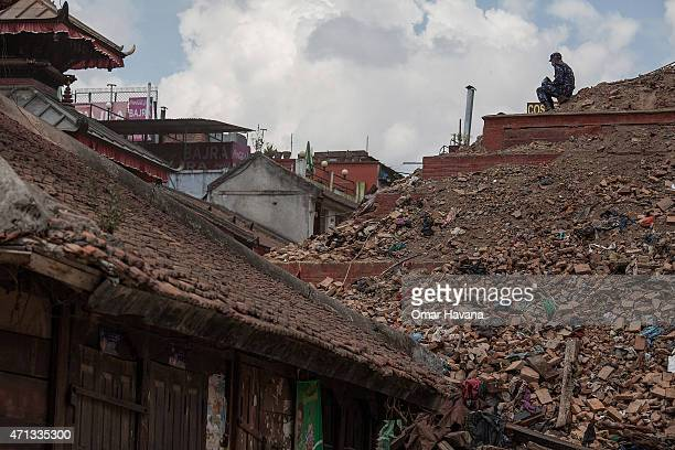 A rescue team member sits on top of the debris of a collapsed temple at Basantapur Durbar Square on April 27 2015 in Kathmandu Nepal A major 78...