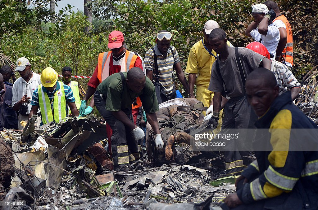 Rescue team members carry the body of a man from the rubble of a plane carrying a military delegation from Guinea that crashed on February 11, 2013 in the Liberian town of Charlesville, killing the army chief of staff and 10 other people. The plane was carrying the delegation to attend an armed forces day in Liberia, which holds ceremonies each year to recognise its military and often invites officers from neighbouring countries, including Guinea. AFP PHOTO / ZOOM DOSSO