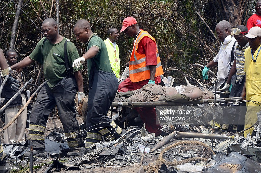 Rescue team members carry the body of a man who was stuck behind one of the engine of a plane carrying a military delegation from Guinea that crashed on February 11, 2013 in the Liberian town of Charlesville, killing the army chief of staff and 10 other people. The plane was carrying the delegation to attend an armed forces day in Liberia, which holds ceremonies each year to recognise its military and often invites officers from neighbouring countries, including Guinea.