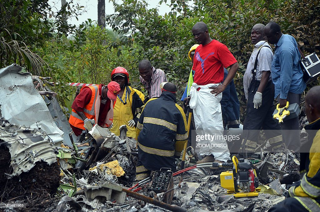 Rescue team members work on the rubble of a plane carrying a military delegation from Guinea that crashed on February 11, 2013 in the Liberian town of Charlesville, killing the army chief of staff and 10 other people. The plane was carrying the delegation to attend an armed forces day in Liberia, which holds ceremonies each year to recognise its military and often invites officers from neighbouring countries, including Guinea. AFP PHOTO / ZOOM DOSSO