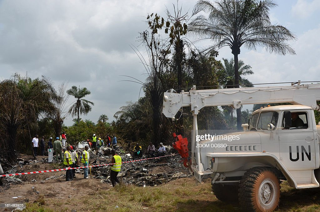 Rescue team members work on the rubble of a plane carrying a military delegation from Guinea that crashed today in the Liberian town of Charlesville, killing the army chief of staff and 10 other people, on February 11, 2013. The plane was carrying the delegation to attend an armed forces day in Liberia, which holds ceremonies each year to recognize its military and often invites officers from neighbouring countries, including Guinea. AFP PHOTO / ZOOM DOSSO