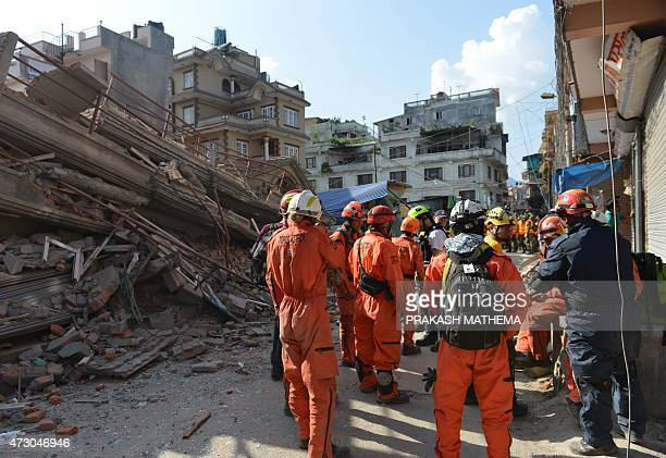 Rescue team officials coordinate as they arrive to search for survivors at a collapsed house in Kathmandu May 12 after an earthquake struck A...