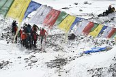 Rescue team personnel carry an injured person towards a waiting rescue helicopter at Everest Base Camp on April 26 a day after an avalanche triggered...