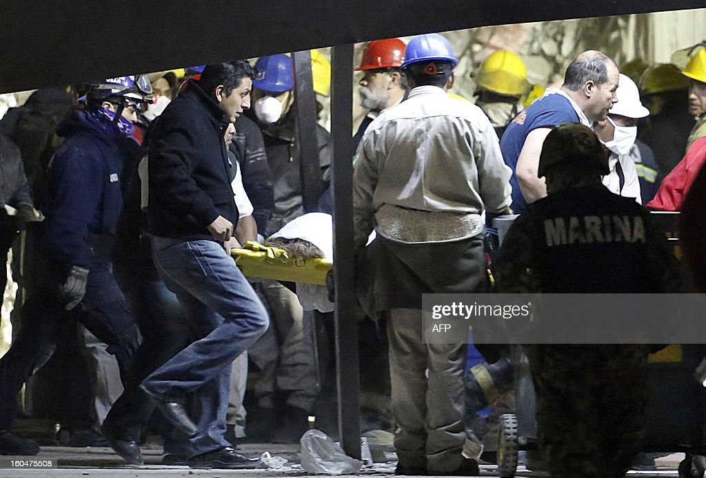 Rescue team recover a corpse from the debris of the headquarters of state-owned Mexican oil giant Pemex in Mexico City on February 1, 2013, following a blast inside the building, leaving up to now 32 dead and 100 injured.