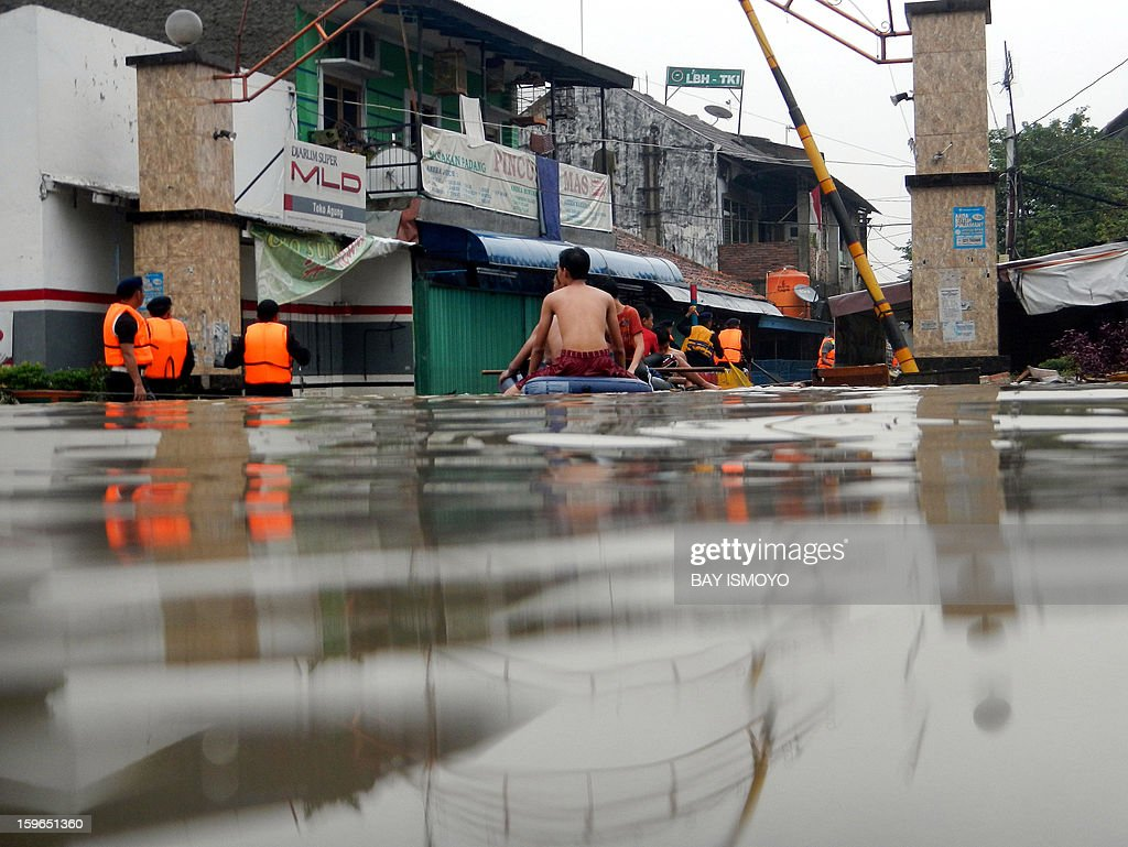 A rescue team (L) tries to find people stuck in their homes in a flooded area of Jakarta on January 18, 2013. Floods in Indonesia's capital Jakarta have left at least 11 people dead, authorities said on January 18 as murky brown waters submerged parts of the city's business district, causing chaos for a second day. AFP PHOTO / Bay ISMOYO