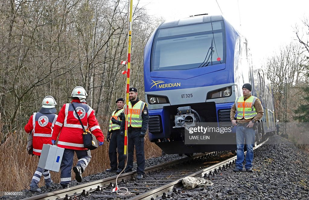 Rescue teams and police work at the site of a train accident near Bad Aibling, southern Germany, on February 9, 2016. Two Meridian commuter trains operated by Transdev collided head-on near Bad Aibling, around 60 kilometres (40 miles) southeast of Munich, killing at least eight people and injuring around 100, police said. The cause of the accident was not immediately clear. / AFP / dpa / Uwe Lein / Germany OUT