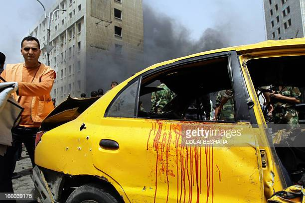 Rescue teams and security forces inspect the scene of a deadly car bomb explosion which rocked central Damascus on April 8 2013 The blast which was...