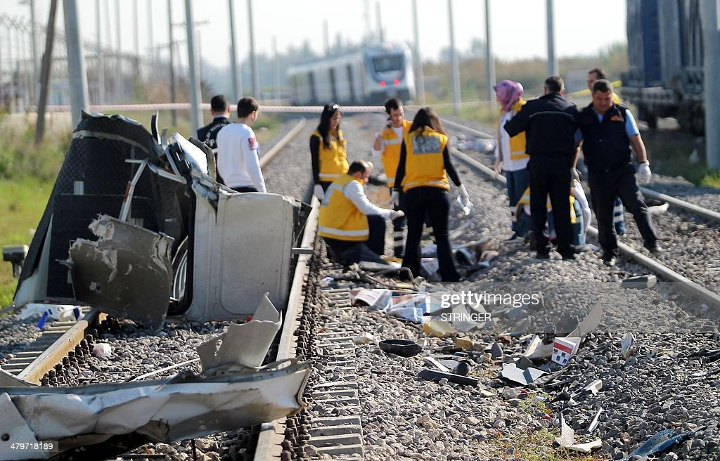 Rescue teams are at work on March 20, 2014 in Mersin after a commuter train smashed into a minibus on a railway track killing 10 people and injuring several others. The bus, which was carrying workers to an industrial zone in the Mediterranean province of Mersin, was hit because the driver proceeded to cross the track 'carelessly', the private Dogan News Agency reported, citing witnesses. AFP PHOTO / ILHAS NEWS AGENCY = TURKEY OUT