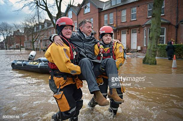 Rescue teams carry people to safety through the flood water as they continue to to evacuate homes after Storm Desmond caused flooding on December 7...