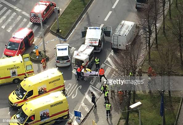 TOPSHOT Rescue teams evacuate wounded people outside the Maalbeek Maelbeek metro station in Brussels on March 22 2016 after a blast at this station...