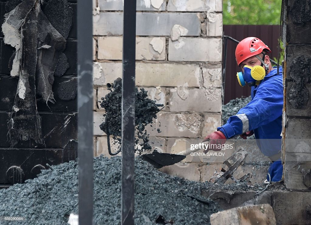 Rescue teams investigate the site of a fire in the village of Litochky, on May 29, 2016. Seventeen people died when a makeshift home for elderly people outside the Ukrainian capital Kiev caught fire in the early hours of May 29, the latest tragedy to shake the conflict-riven country. The fire tore through the two-storey shelter for the elderly which is in the village of Litochky, located some 50 kilometres (31 miles) north of Kiev. / AFP / GENYA