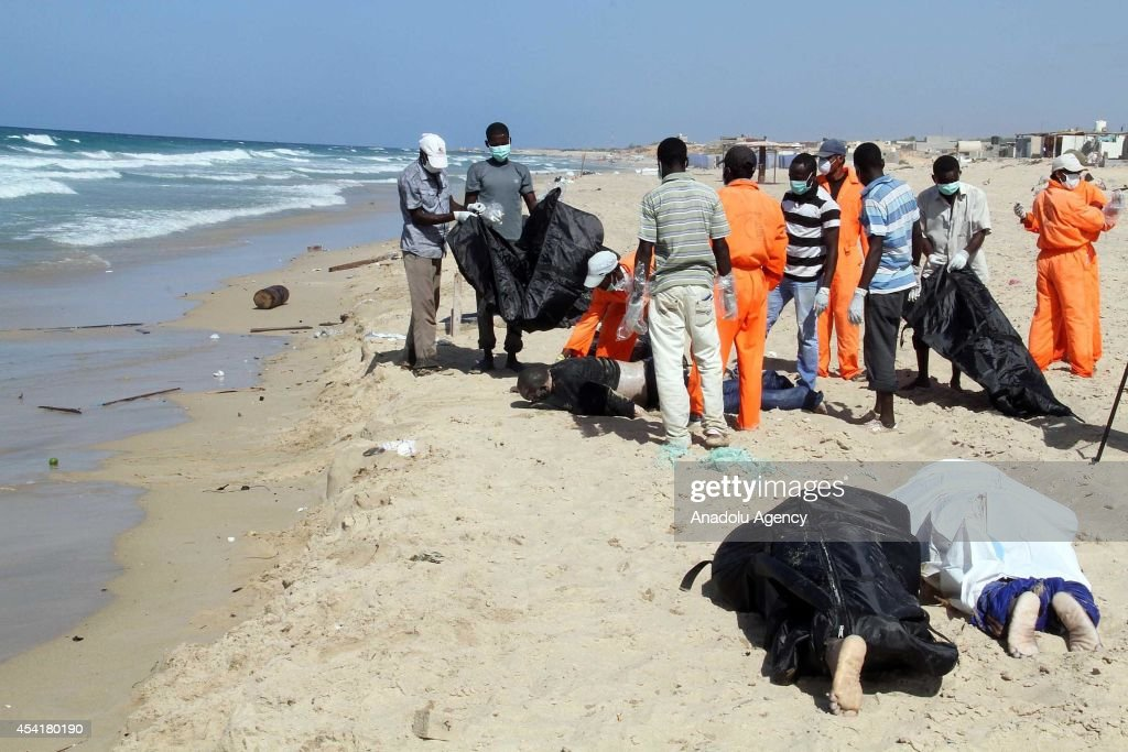 Rescue teams try to remove dead body of refugees in Libya on August 25, 2014. An overloaded boat carrying suspected illegal African immigrants sank and at least 200 passengers drowned, many of them missing.