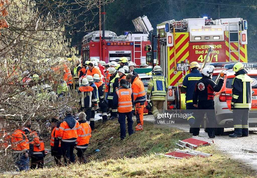 Rescue teams work at the site of a train accident near Bad Aibling, southern Germany, on February 9, 2016. Two Meridian commuter trains operated by Transdev collided head-on near Bad Aibling, around 60 kilometres (40 miles) southeast of Munich, killing at least eight people and injuring around 100, police said. The cause of the accident was not immediately clear. / AFP / dpa / Uwe Lein / Germany OUT