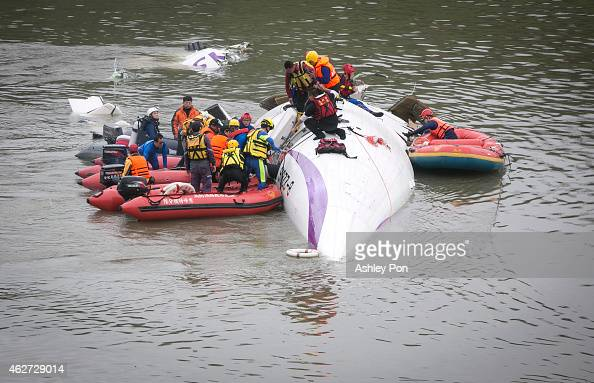 Rescue teams work to free people from a TransAsia Airways ATR 72600 turboprop airplane that crashed into the Keelung River shortly after takeoff from...