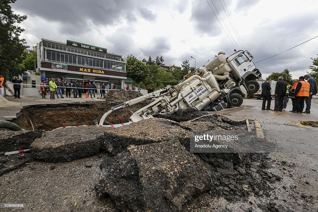 A rescue vehicle, belonging to metropolitan municipality falls into a hollow, occurring after softened ground due to a bursted waterpipe, as it tries to rescue a car, which felt into same hallow three hours ago in Ankara, Turkey on May 6, 2016.