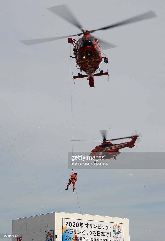 A rescue worker abseils from a helicopter during the firefighting demonstration at the annual new year fire review in Tokyo on January 6, 2013. A total of 2,800 fire fighters, 133 vehicles, 5 helicopters and 8 boats participated in the new year firefighting exercises.