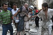 A rescue worker and residents carry an injured man following a reported air strike by Syrian government forces on July 27 2014 in the northern city...