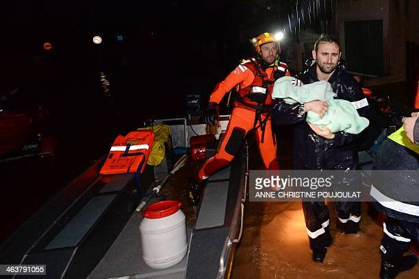 A rescue worker assists a man carrying his child as people are evacuated from their homes in the Oratoire neighborhood of HyeresLesPalmiers on...