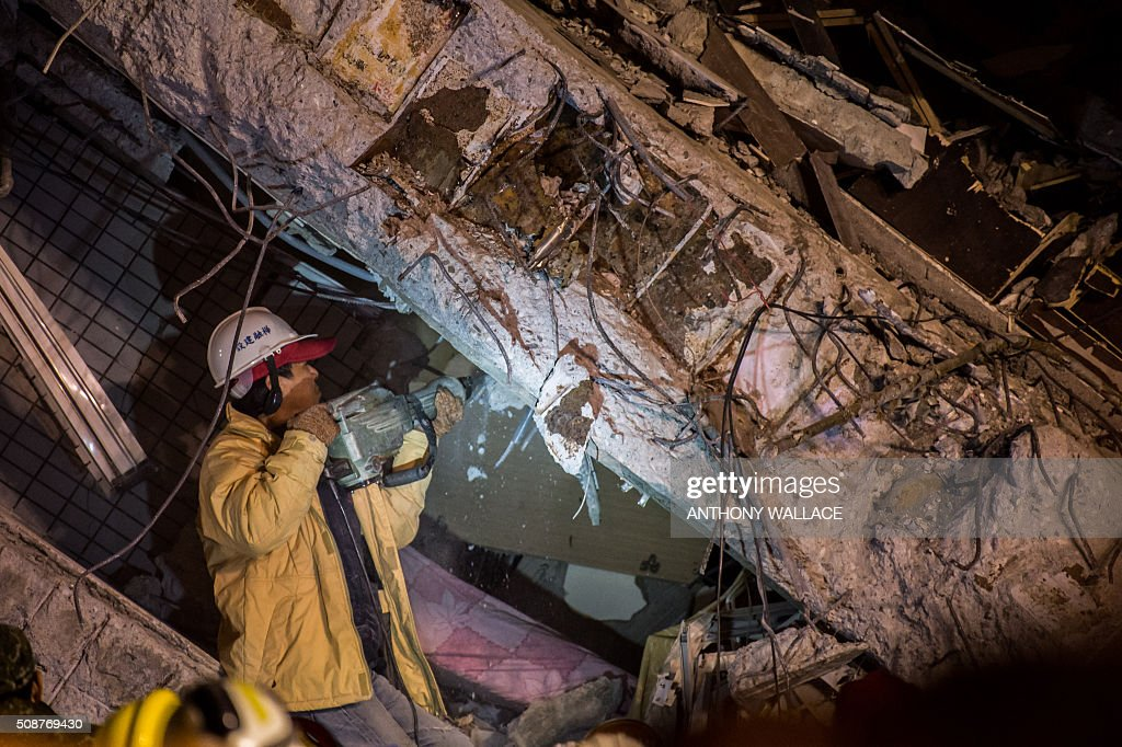 A rescue worker breaks down rubble of a collapsed building in the southern Taiwanese city of Tainan following a strong 6.4-magnitude earthquake that struck early on February 6, 2016. Relatives of residents trapped in a 16-storey apartment complex felled by a powerful earthquake in Taiwan that killed 14 people were praying for miracles Saturday as rescuers sought survivors, with more than 150 missing in the quake zone. / AFP / ANTHONY WALLACE