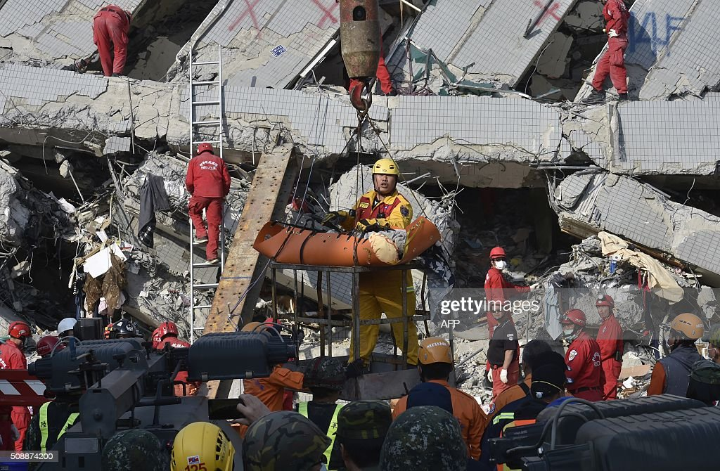 A rescue worker brings down a victim from the collapsed Wei Kuan complex building in Tainan, southern Taiwan, on February 7, 2016, following a strong 6.4-magnitude earthquake that struck early on February 6. Rescuers raced on February 7 to free more than 120 people buried under the rubble of an apartment complex felled by an earthquake in southern Taiwan that left 24 confirmed dead, as an investigation began into the collapse. AFP PHOTO / Sam Yeh / AFP / SAM YEH