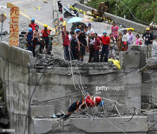 A rescue worker carries a fouryearold boy over a fallen bridge through a cable in Hsinfa a remote village in Taiwan's southern Kaohsiung county on...