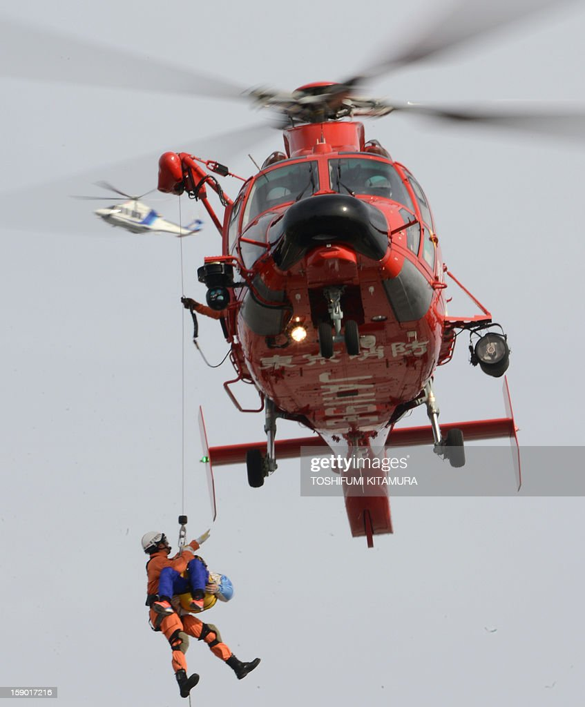 A rescue worker carries a victim onto the helicopter during the firefighting demonstration at the annual new year fire review in Tokyo on January 6, 2013. A total of 2,800 fire fighters, 133 vehicles, 5 helicopters and 8 boats participated in the new year firefighting exercises.