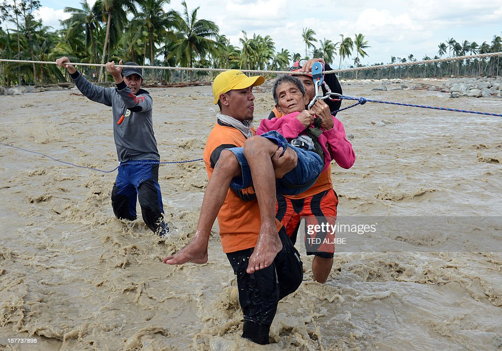 A rescue worker carries an elderly resident across a surging river in New Bataan, Compostela Valley province on December 6, 2012, two days after Typhoon Bopha hit the province. A quarter million people were homeless and 477 confirmed dead after the Philippines' worst typhoon this year, officials said on December 6, as the government appealed for international help.