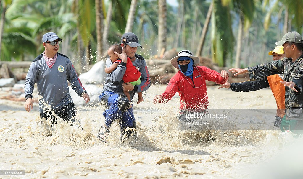A rescue worker carries the child of Lenlen Medrino across a surging river in the town of New Bataan, compostela province on December 6, 2012. Nearly 200,000 people are homeless and more than 300 dead after the Philippines suffered its worst typhoon this year, authorities said on December 6, reaching out for international aid to cope with the scale of the disaster.