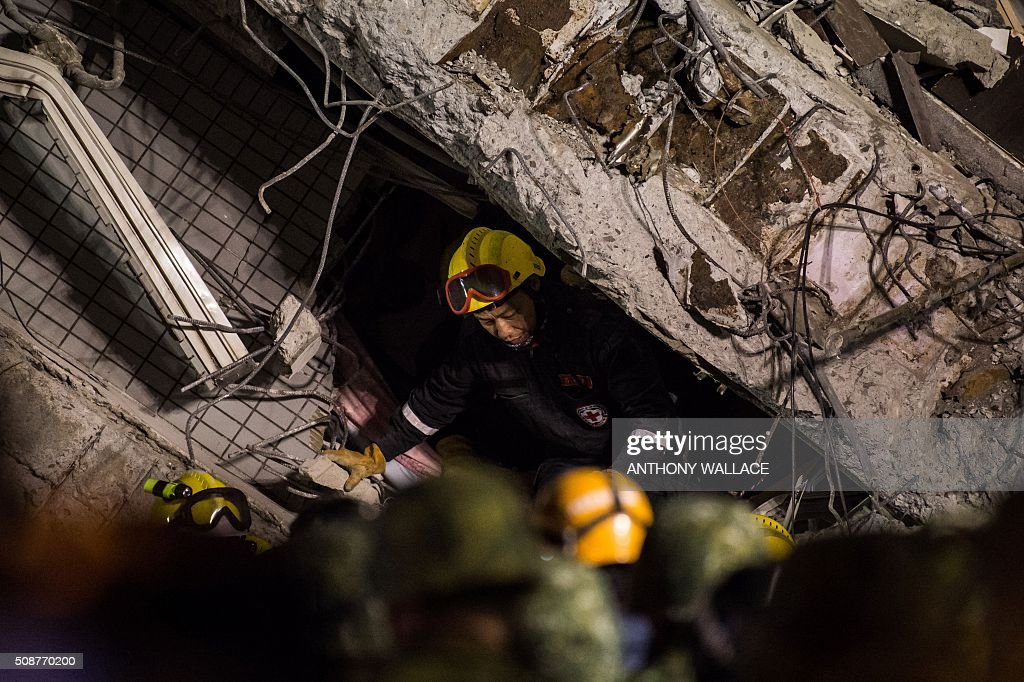 A rescue worker crawls out of a collapsed building in the southern Taiwanese city of Tainan following a strong 6.4-magnitude earthquake that struck early on February 6, 2016. Relatives of residents trapped in a 16-storey apartment complex felled by a powerful earthquake in Taiwan that killed 14 people were praying for miracles Saturday as rescuers sought survivors, with more than 150 missing in the quake zone. / AFP / ANTHONY WALLACE