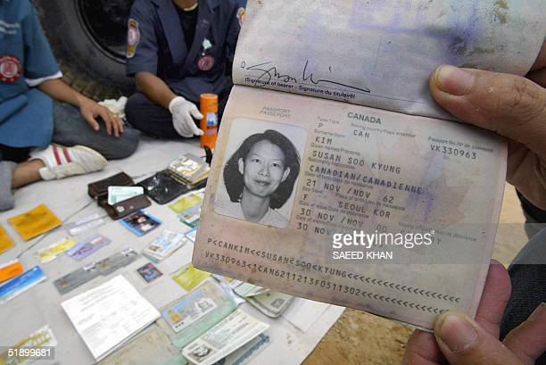 A rescue worker displays the passport of Canadian national Susan Soo Kyung after collecting it from the debris in Khao Lak 29 December 2004 as...