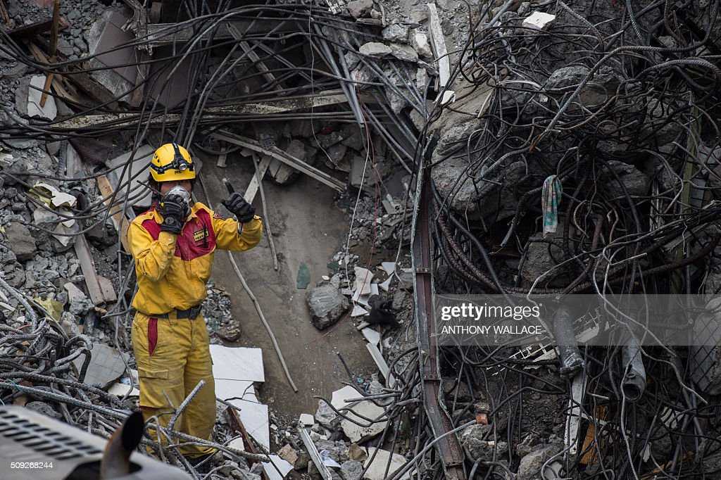 A rescue worker (C) gestures while using a walkie-talkie on what was the top of the Wei-Kuan complex which collapsed in the 6.4 magnitude earthquake, in the southern Taiwanese city of Tainan on February 10, 2016. The developer of a Taiwan apartment complex that collapsed during a strong earthquake was arrested, as rescuers reported hearing signs of life in the rubble where some 100 people are still trapped. AFP PHOTO / ANTHONY WALLACE / AFP / ANTHONY WALLACE